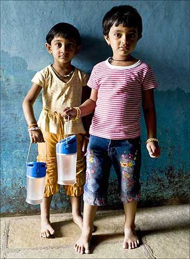Children holding the Kiran lamp in India.