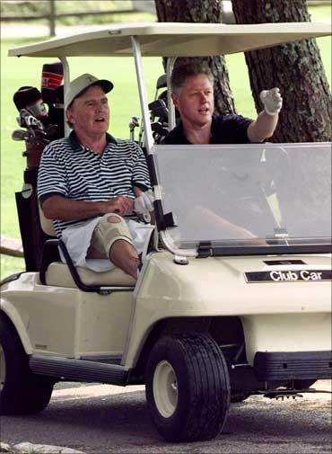 The then US president Bill Clinton explains the layout of the first hole to General Electric CEO Jack Welch (L).