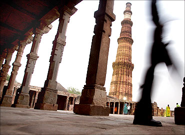 A tourist walks past the Qutab Minar in New Delhi.