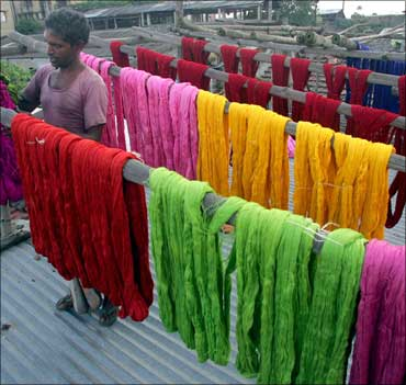 A worker arranges coloured skeins of yarn on a roof at a hand-dyeing factory.