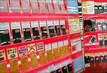 A woman looks at Japan's top mobile phone operator NTT DoCoMo handsets in Tokyo.