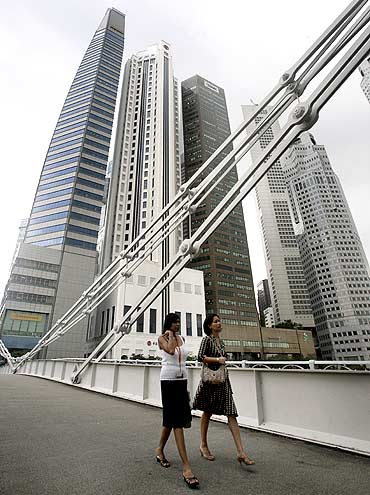 Office workers cross a bridge in Singapore's financial district.