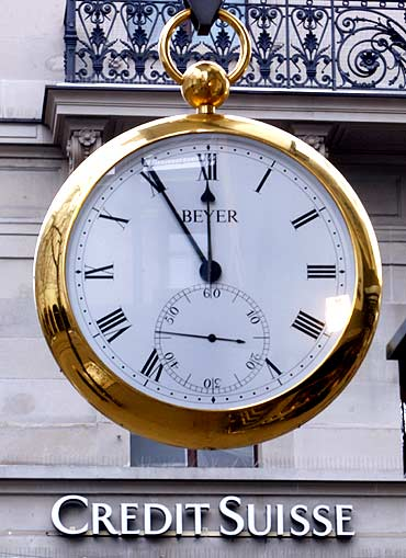 A giant watch displays the time in front of the logo of Swiss Credit Suisse bank.