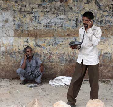 Two men speak on telephones at a roadside telephone booth in New Delhi.