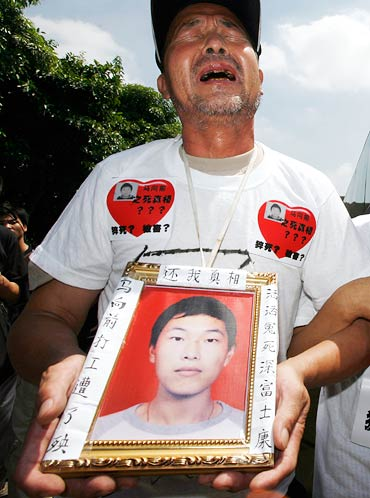 Ma Zishan cries as he carries a portrait of his son Ma Xiangqian outside a Foxconn factory.