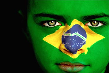 A lady shows the Brazilan flag on her face.
