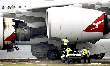 Technicians work next to the damaged engine of a Qantas Airways A380 passenger plane.
