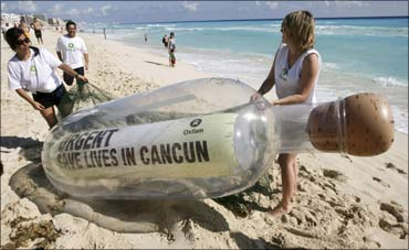 Activists of Oxfam carry a giant bottle on the shores of a beach in Cancun. The bottle contains a message reading 'Urgent: Save Lives in Cancun', in reference to millions of world's poorest people. Photograph: Stringer/Reuters
