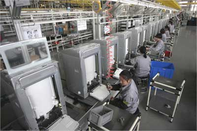 Employees work at a washing machine production line.