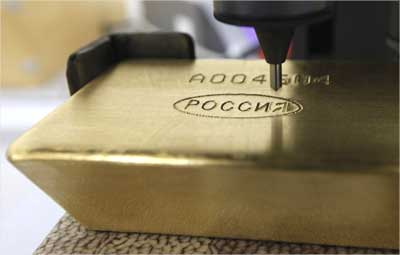 A machine engraves information on an ingot of 99.99 percent pure gold.