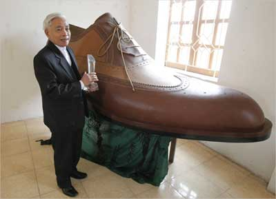 Luu Xuan Chung stands next to 2.72 metre Italian-style shoe in the handicraft village of Gie Ha.