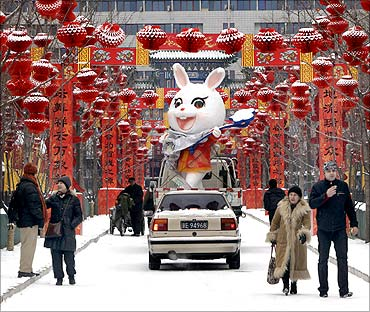 A rabbit sculpture is carried away from the Ditan temple fair after a snowfall in Beijing.