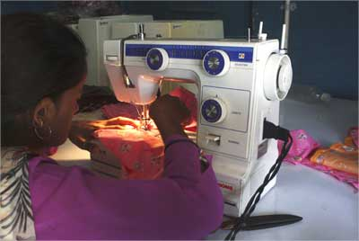 A woman sews clothes on a sewing machine driven by solar energy in Ahmedabad.