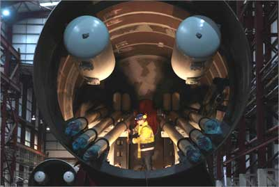 An engineer works inside a section of a Pelamis wave energy converter at their factory in Edinburgh, Scotland.