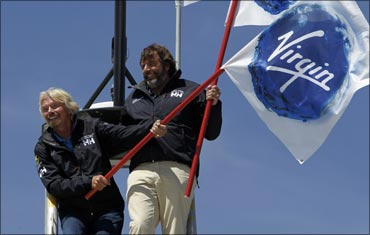 Branson (L) and Chris Welch stand on the crows nest of the Cheyenne, a 125 ft catamaran.
