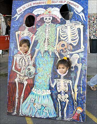 Two children have their picture taken during a celebration of the Day of the Death in Los Angeles.