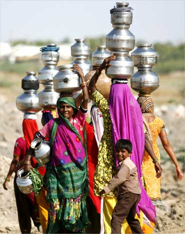 Villagers carry pitchers filled with drinking water in Gujarat.