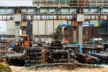 Workers at JFE Steel Corp's facility in an area devastated by the March 11 earthquake and tsunami, in Sendai, Miyagi prefecture.