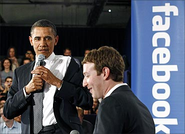 Obama takes off his jacket as he attends a town hall meeting at Facebook headquarters.