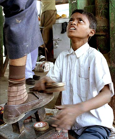 A boy polishes shoes at a suburban railway station in Mumbai.