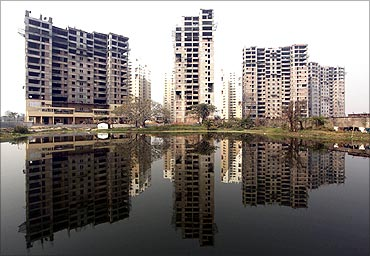 Residential apartments under construction are reflected on the surface of a pond in Kolkata.