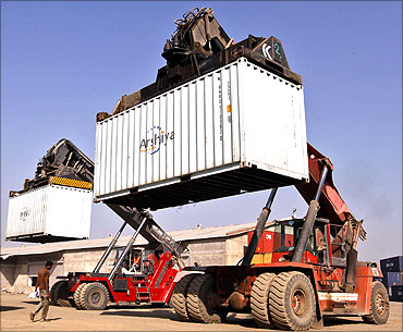 Workers prepare to stack containers using cranes at Thar Dry Port in Sanand in Gujarat.