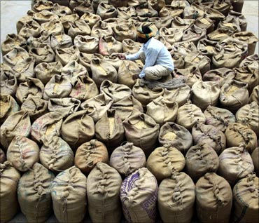 A worker prepares sacks of grain at a wholesale market at Dadri.
