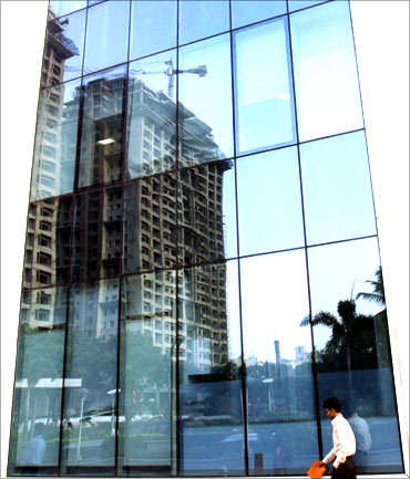 A man walks past a building reflecting the construction of other buildings in Mumbai.
