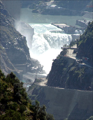Water flows on the banks of Chenab River with the Baglihar hydroelectric project in the background.
