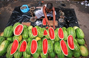 A vendor arranges watermelons for sale in a pavement stall in Kolkata.