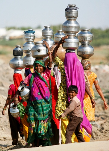 Villagers carry pitchers filled with water after visiting a well at Meni village in Gujarat.