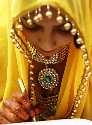 A bride makes an entry during a mass marriage ceremony in Ahmedabad.