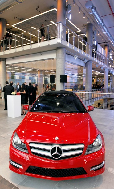 Attendees stand in the showroom of a new Mercedes-Benz dealership during a gala to celebrate its opening in New York.