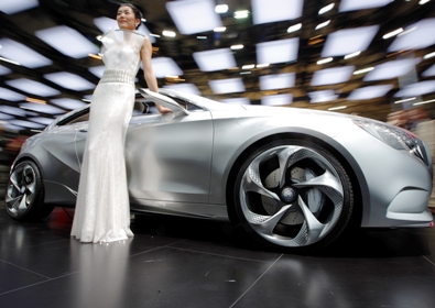A model poses next to a Mercedes Benz Concept A-Class at the Shanghai Auto Show,