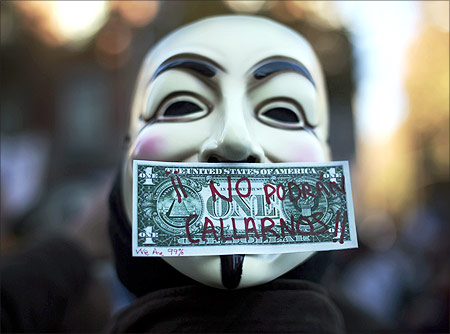 A protester wearing a Guy Fawkes mask, symbolic of the hacktivist group Anonymous, is pictured with a fake dollar bill.