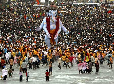 Devotees carry a statue of the Hindu elephant god Ganesh, the deity of prosperity.