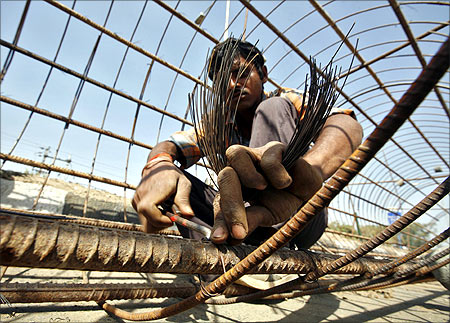 A labourer works on reinforcing bars at a construction site to build a bridge.