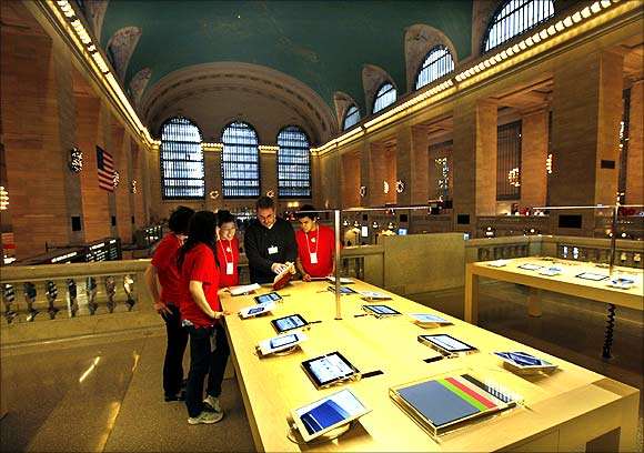 Employees look at iPad tablets on display inside the newest Apple Store in New York City's Grand Central Station.
