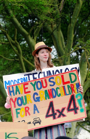 Environmental activist holds up a sign during a demonstration.
