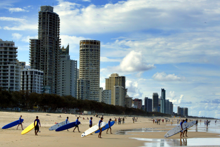 Longboard surfers walk into the water at Surfer's Paradise, 60 kilometres southeast of Brisbane.