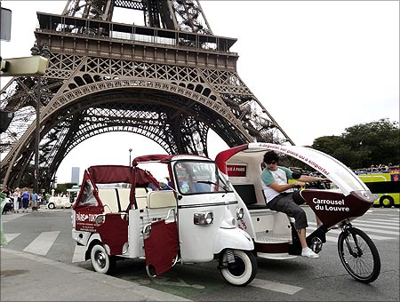 A velo taxi (R), or bicycle taxi, drives past a tuk-tuk, or three wheeled auto rickshaw, near the Eiffel tower in Paris.