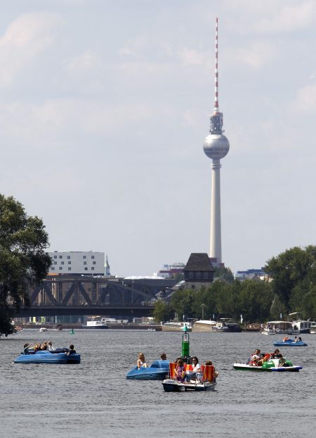 People use paddleboats on the river Spree during a sunny day in Berlin.