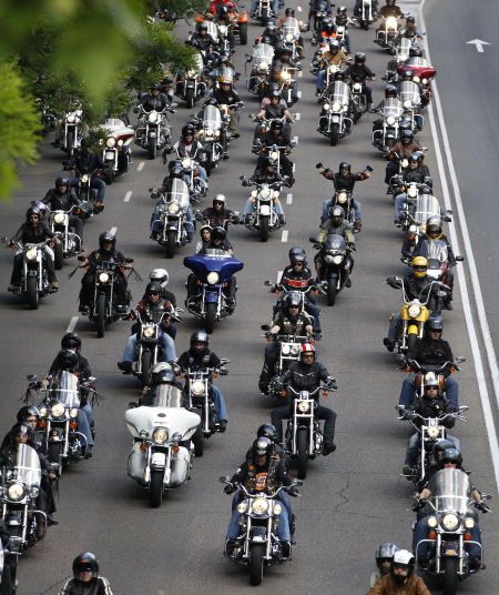 Motorcyclists ride down the central avenue in Madrid.