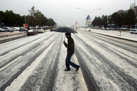 A man walks on a road after heavy rain and a hailstorm hit Islamabad.