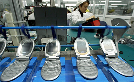 A Chinese worker tests mobile phones at Ningbo Bird Co. Ltd production line.