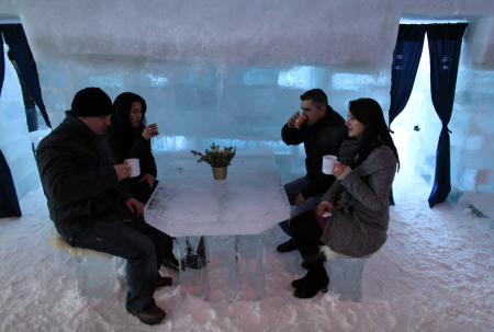 Tourists sit at a table serving warm drinks inside the Balea Lac Hotel of Ice in the Fagaras mountains.