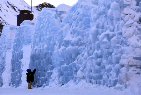 A child touches the outside wall of the Balea Lac Hotel of Ice in Fagaras mountains.