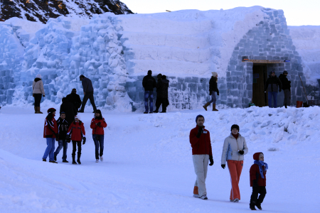 Tourists walk in the snow outside the Balea Lac Hotel of Ice in Fagaras mountains.