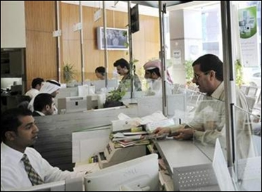 Bank tellers are seen interacting with customers at the Dubai Islamic Bank in Dubai.