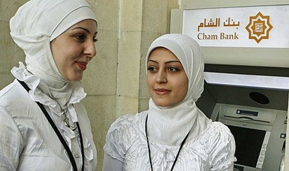 Employees of Cham bank, a newly opened Islamic bank, stand in front of an ATM machine.